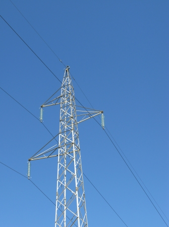 An electricity mast opposite a blue sky photo