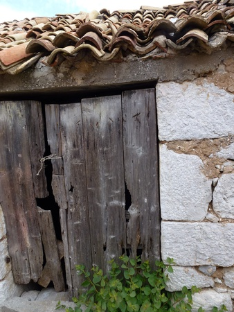 An old barn with a wooden door and orange tiles photo