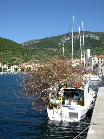 Piled fish traps on a small fishing boat in the harbor of Komiza on the island Vis in Croatia photo