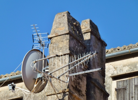Chimney of stone with an antenna and a satellite dish photo