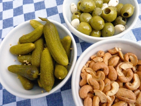 Cashew nuts, green olives and gherkins photo