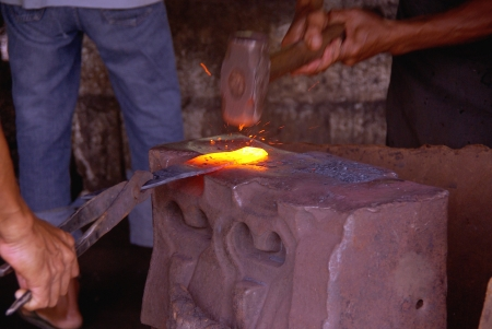 A blacksmith at a anvil photo