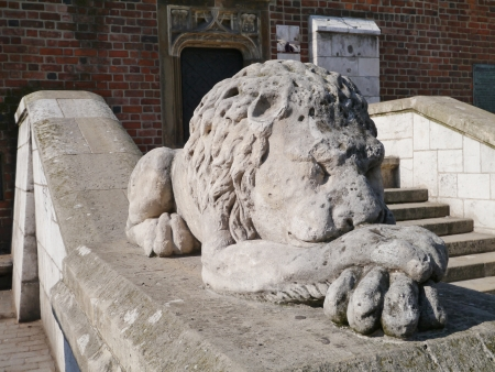 A sculpture of a sleeping lion on a wall of a stairway photo