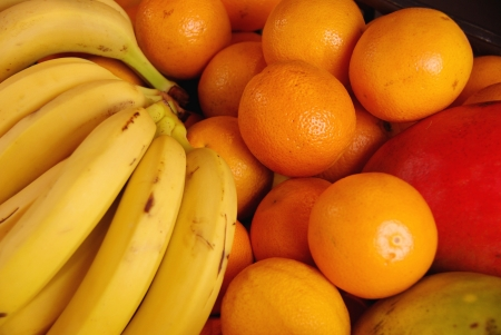 Bananas, oranges and mangoes at the greengrocer on the market place photo