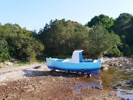 A blue fishing boat ashore on an Croatian island in the Mediterranean photo