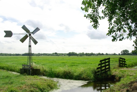A water mill along a ditch with a wooden gate in a dutch landscape at the countryside in the Netherlands Stock Photo - 16889522
