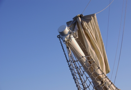 cordage: A bowsprit with a sail as a silhouette against a blue sky