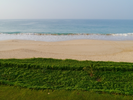 The beach of Koggala in Sri Lanka with breakers in the Indian ocean and green plants Stock Photo - 17854725
