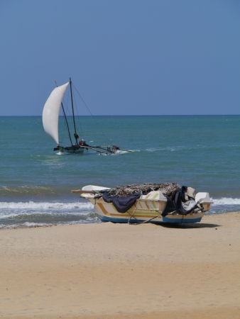 A sailing traditional fishing boat and a modern boat on the beach in Sri Lanka Stock Photo - 17852278
