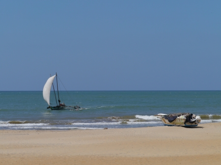A sailing traditional fishing boat and a modern boat on the beach in Sri Lanka Stock Photo - 17819563