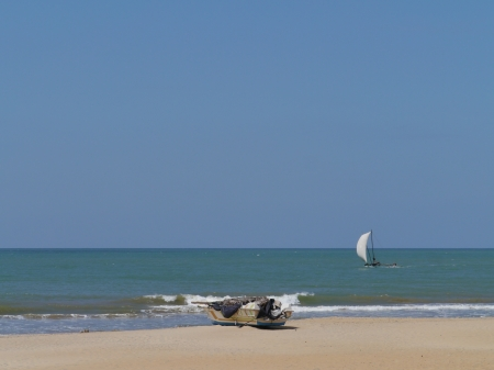 A sailing traditional fishing boat and a modern boat on the beach in Sri Lanka photo