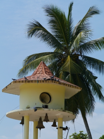 The bell tower and a palm tree at the Wewurukannala Vihara temple in Sri Lanka Stock Photo - 18216386