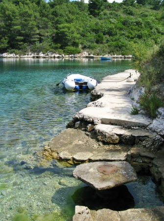 The colors of a rocky coast with a dinghy in a bay in the Adriatic sea of Croatia photo
