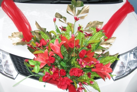 Red flower arrangement for a wedding on a car
