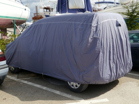 A car under a grey protection cover Stock Photo - 19220656