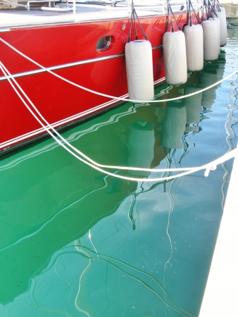 buffers: A red sailing yacht with fenders in a marina Stock Photo