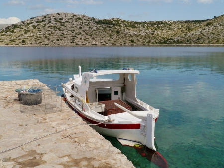 Piled fish traps of a small fishing boat in the bay of the island Levrnaka in the Kornati national park in Croatia photo