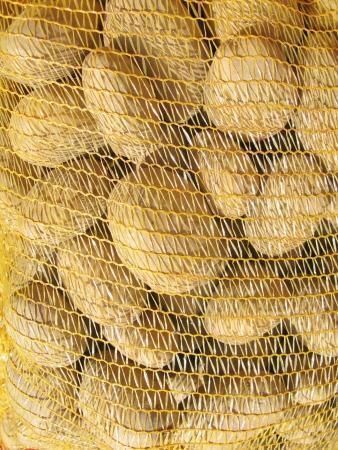 greengrocer: Patatas en una red en la verduler�a en el mercado Foto de archivo
