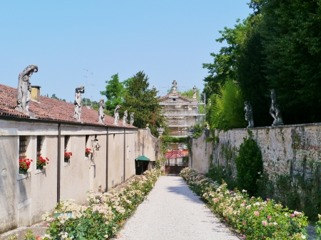 entranceway: The outbuildings with statues on the roof along the entranceway to the villa Rotonda near Vicenza in Italy