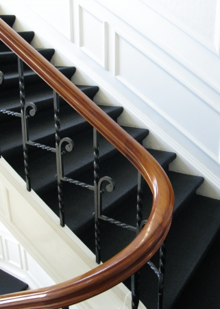 stair well: A majestic staircase with a wooden railing and wall decorations