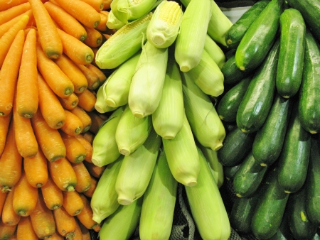 Carrots indian corn and courgettes at the greengrocer on the market place photo