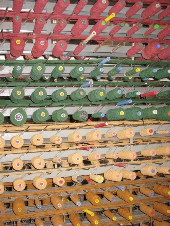 Cylinders with red green and yellow wool threads for a weaving loom in Geelong in Australia photo