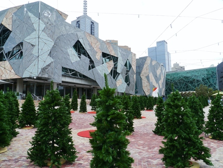 view of an atrium in a building: Federation square in Melbourne in Australia with artificial green christmas trees in summer