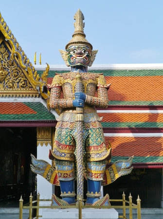 A waiter of colorful mosaic in front of one of the buildings of the historic Royal or Grand palace in Bangkok in Thailand photo