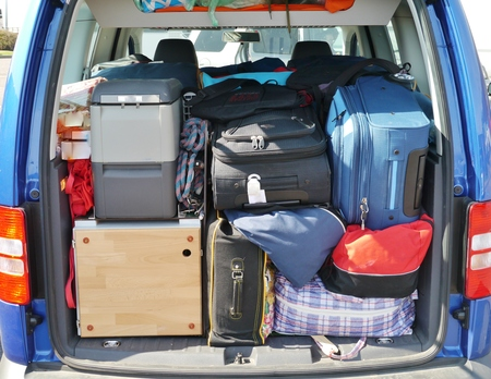Suitcases and bags in the luggage boot of a car photo