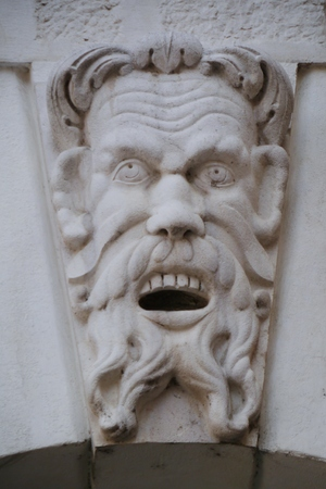 grotesque: A face of a man as decoration on the historic loggia in Brescia in Italy Stock Photo