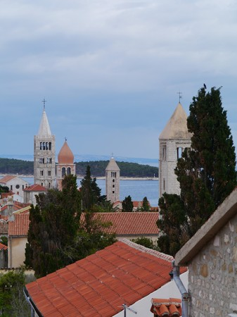 The four church towers of the city Rab in Croatia photo