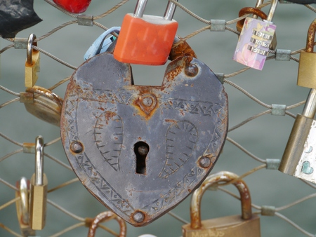 passe: A rusty metallic padlock shaped as a heart passed through a bridge and without a key in Graz in Austria Stock Photo