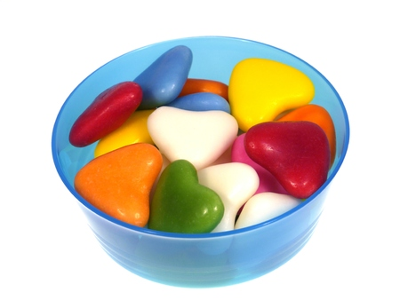 laxative: Many colorful heart sugar candies in a blue plastic bowl over white Stock Photo