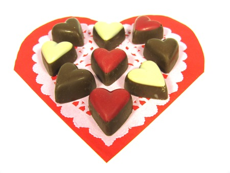 Chocolates on an lace paper and a red heart over white photo