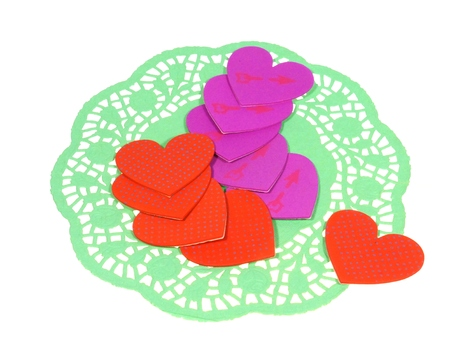 doiley: Isolated green filigree paper with red and magenta hearts as a Valentines day decoration