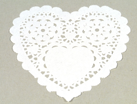 doiley: A filigree paper heart over a grey background
