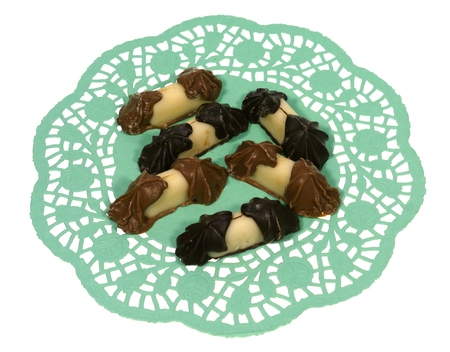 doiley: Chocolate and marzipan on a green filigree doily paper over white Stock Photo