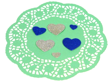 doiley: Isolated green filigree paper with silver and blue hearts as a Valentines day decoration