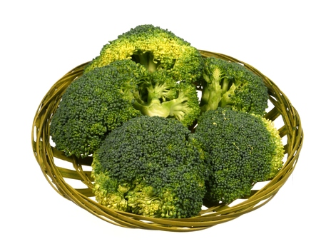 Fresh broccoli in a green basket over white photo