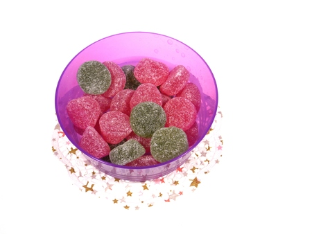 doiley: Sugar candies in a plastic bowl on a paper lace over white