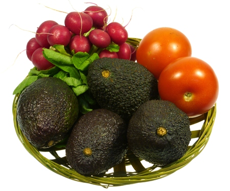 hass: A basket  with avocadoes or alligator pears, radishes and tomatoes over white Stock Photo