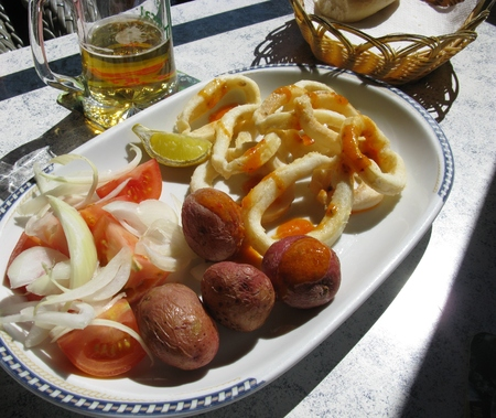 mojo: Squid rings with Canary Island potatoes topped with a red mojo sauce and a salad of tomatoes and onions served on a white plate Stock Photo