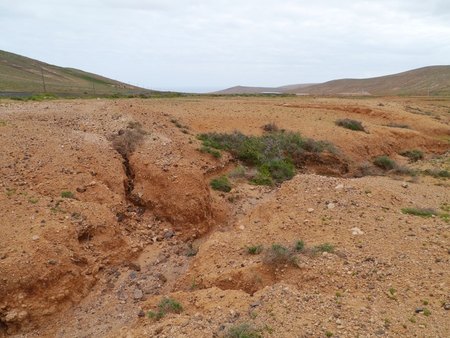 surroundings: Dry creeks and river beds form the red earth in the surroundings of La Oliva on the island  Fuerteventura  in Spain Stock Photo