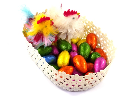 Colorful Easter eggs of chocolate and two decorative chickens in a basket over white Stock Photo