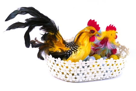 An Easter chicken and a cock in a basket with artificial eggs