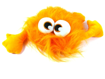 bulging: Orange toy monster with long hair and bulging eyes as a soccer mascot over white