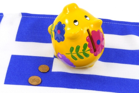 greek coins: An empty piggy bank on the Greek flag with small euro coins