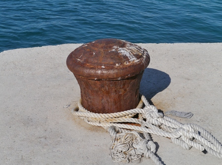 the mainland: Rusty mooring bollard with ship ropes at the quay of the city Biograd at the mainland of Croatia