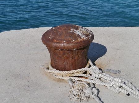 mooring bollards: Rusty mooring bollard with ship ropes at the quay of the city Biograd at the mainland of Croatia