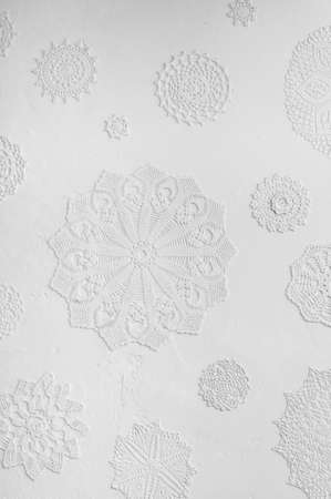 doilies: blurry crocheted doilies in gesso on white wall Stock Photo